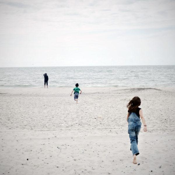 Niños en la playa corren hacia el mar