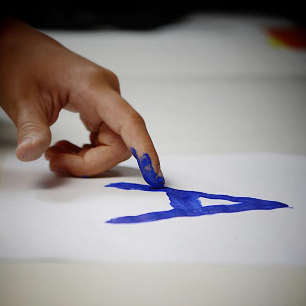 Mano de niño escribiendo una A con el dedo indice