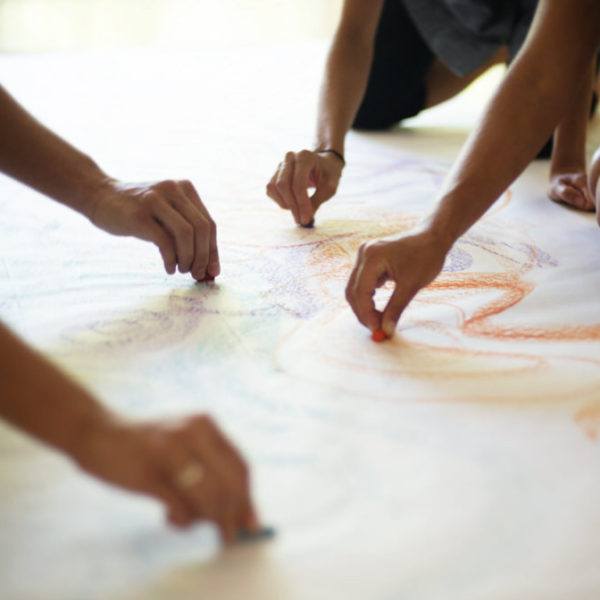 manos de niños dibujando con tiza