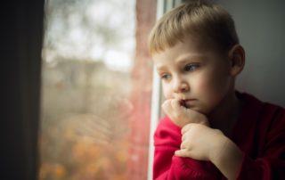 Niño mirando por la ventana
