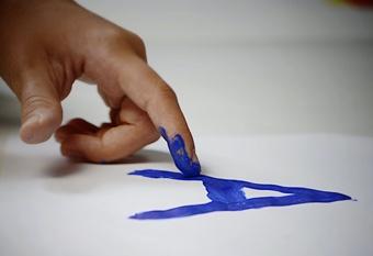 Niño dibuja una letra azul con el dedo